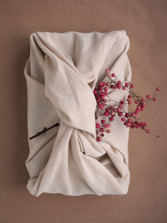 Detalhe de uma embalagem da foto anterior, que possui várias. Aqui só se vê uma embalagem com amarração de tecido bege, um galho de pimenta-rosa (são bolinhas vermelha pequenas) sem folhas. Ela está em cima de uma folha de papel marrom.