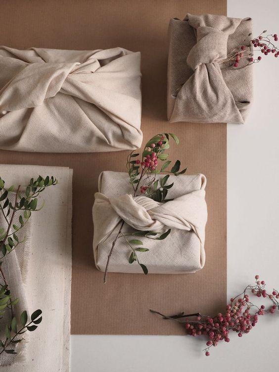 Quatro embalagens feitas com tecido, como se fosse uma trouxinha de comida. Os tecidos são bege, tons clarinhos. As embalagens estão dispostas em cima de um papel ou madeira marrom e possuem galhinhos de pimenta-rosa enfeitando no nó da embalagem.