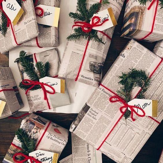 Muitas caixinhas de diversos tamanhos embaladas com jornal, fechadas com um barbante vermelho bem vivo, uma plantinha que parece um pinheiro e tags com nomes de para quem são os presentes