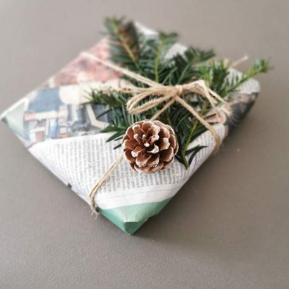 Embalagem de presente, um retangulo, feita de jornal com um barbante e plantinhas e uma pinha presas ao barbante.
