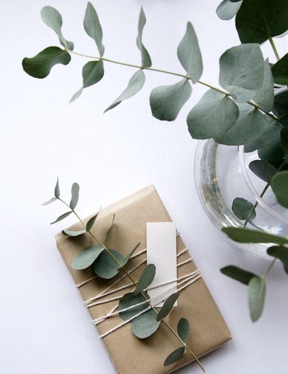 Uma embalagem de presente com papel pardo, barbante no meio do pacote passado varias vezes e uma folhinha de eucalipto e um bilhetinho presos no barbante. do lado do pacote se vê um vaso com galhos de eucalipto.