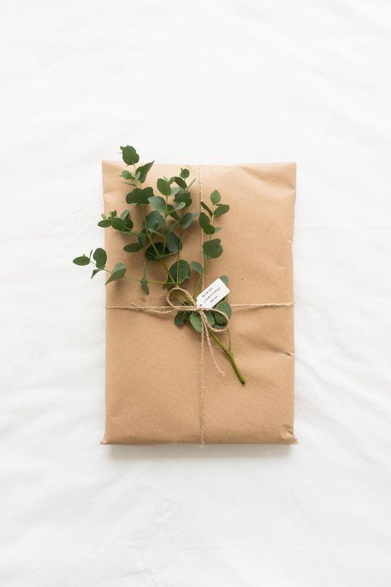 Um pacote de presente de papel pardo com um barbante amarrando e um galhinho verde de alguma planta. A foto é de cima e o pacote está em cima de um tecido branco.