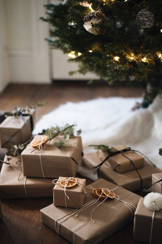 Uma árvore de natal no fundo e na frente, vários pacotes de presente embrulhados com papel pardo, barbante e uma folha ou laranja pra decorar o pacotinho